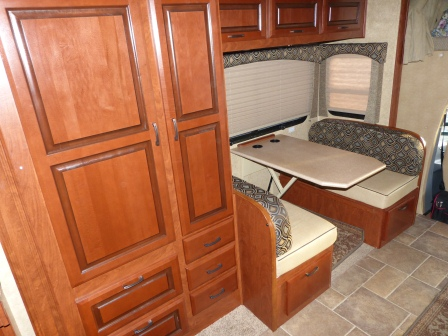 Closet, panty, and drawers in cheery wood besider a 4 person dinette