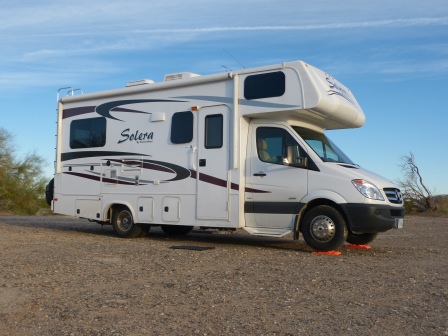 Passenger side of white motorhome on flast desert ground taken from low angle