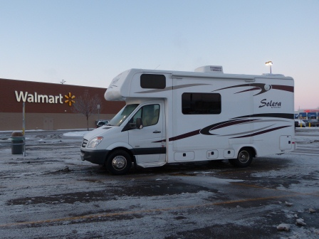 RV in a frosty parking lot with Walmart behind