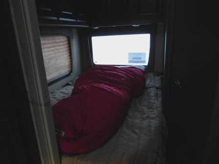 A warm thick red sleeping bag on our RV bed
