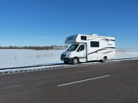 Motorhome beside road with flat, snowy prairie int he background