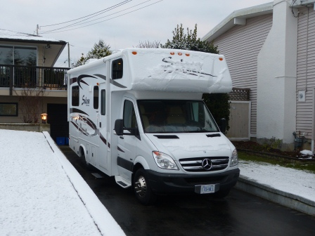 White RV in a driveway with snow on the ground