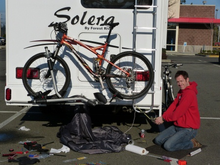 Patrick kneeling at rear of motorhome working on lights and wiring
