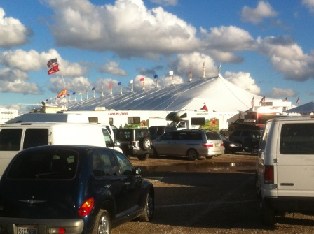 Large white tent with multi-coloured flags on top and parked crs in the foreground