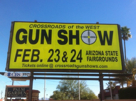 Yellow billboard with black writing adversing the Gun Show