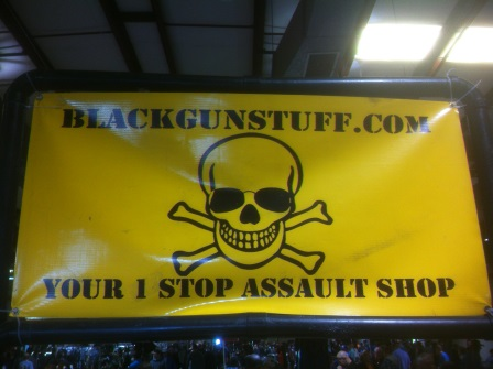 "A large yellow sign with a skull and crossbones saying ""Blackgunstuff.com, Your 1 Stop Assault Shop"""