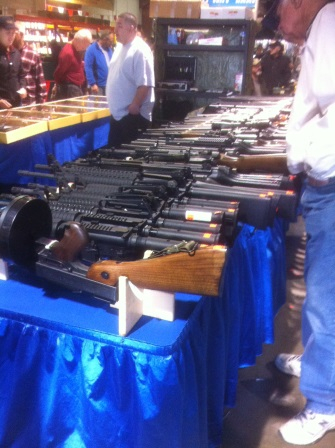 A lont of long guns for sale, laying on a table
