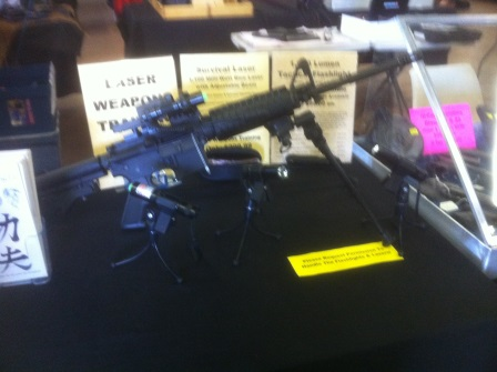 Large black rifle with legs sitting on a table