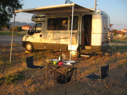 Our RV with awning extended with dinner table and chairs set outside