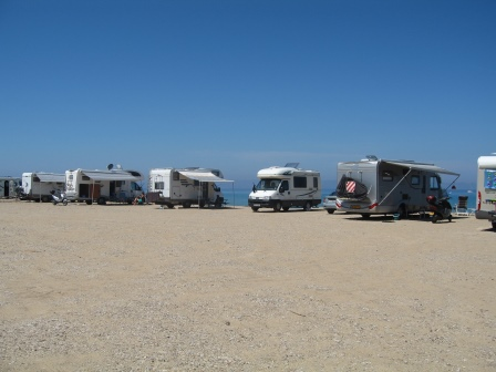 Our RV in a line with others in a sand parking lot on the beach