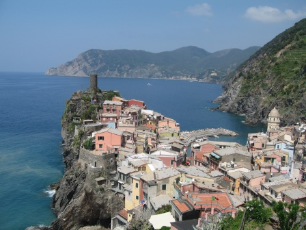 Village with coloured houses on a cliff jutting out into the ocean