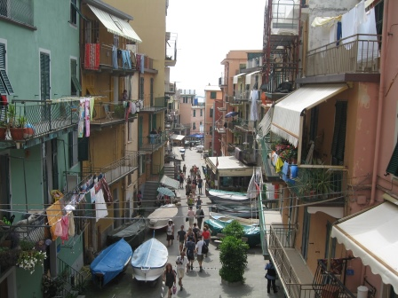 A narrow streat filled with people with balconies and awnings on both sides