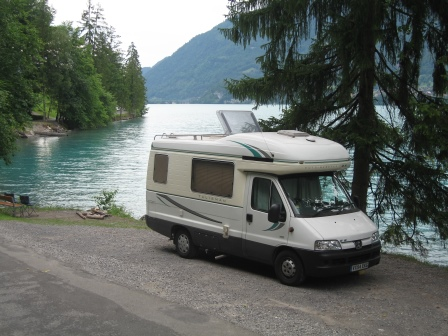 Our white RV parked beside a Swiss lake
