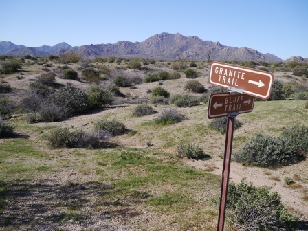 A desert landscape with small mountains in the background and a sign post intersection in the foreground