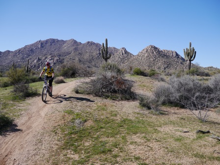 A trail in the desert with Diane riding her mountain bike on the left side and small rocky mountains in the background