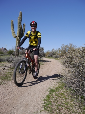 Patrick riding his mountain bike on a dirt trail with a large Saguaro cactus behind