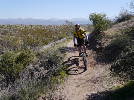 Kiving riding his bike down a short dirt hill with desert in the background