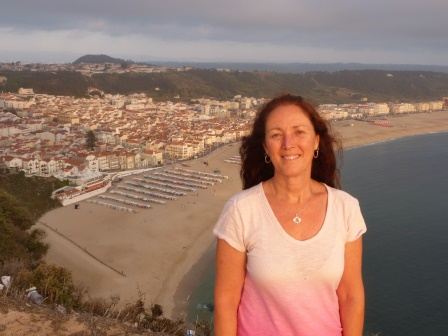 Diane at sunset with a long sandy beach and buildings below ni the distance