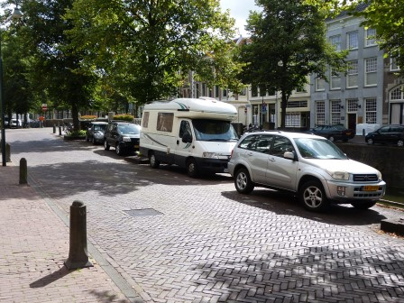 OUr white RV parked beside a canal with cars in front and back