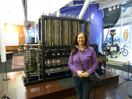 Diane standing in front of large metal, mechanican device
