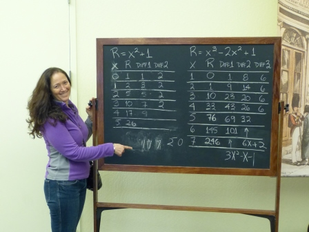 Diane pointing to a blackboard with a tables of 2 simple polynomials