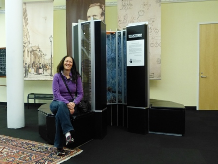 Diane seated on bench of a 2 meter high cyclindrical computer