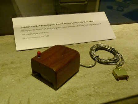 A small wooden box with a button on top and a cord extneding