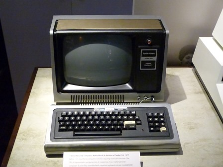 Balck computer sitting in front of a black and white television