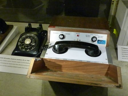 A telephone handset sitting on white cradel