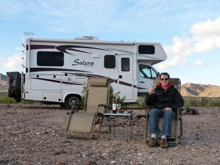 Patrick seated in front of motorhome in reclining lawn chair with martini in hand