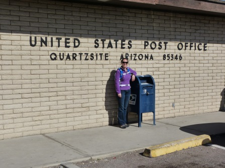 Diane standing in front of post office bside a post office box wearing purple fleece with sign behind