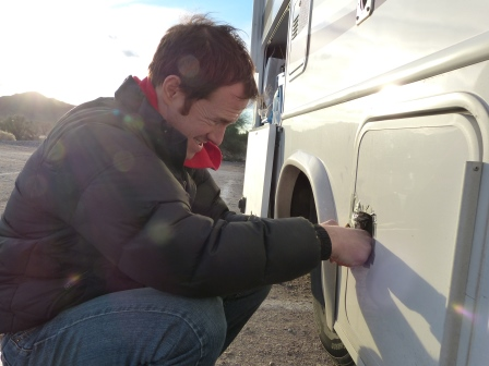 Patrick working on latch of motorhome compartment
