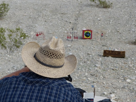 Looking over the shoulder of a man wearing a couwboy had with targets in the distance on a sand hillside