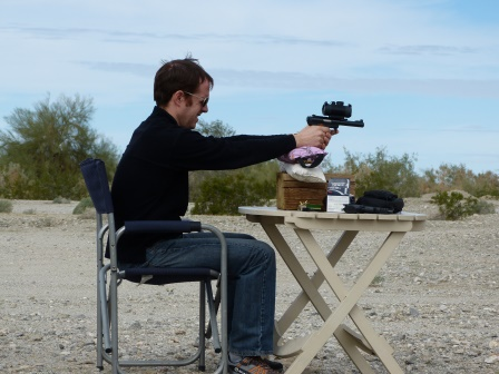Patrick firing a target pistol with a large sight