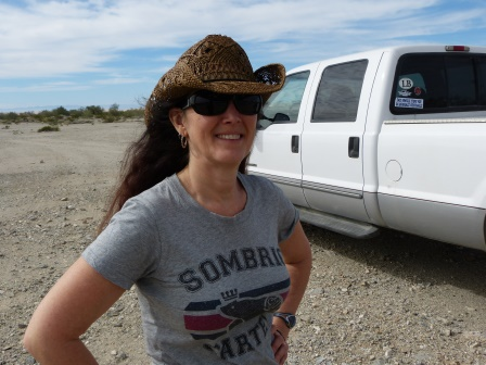 Diane standing looking relieved with white pickup truck in background