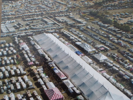 Aerial photo of large white tent surrounds by motorhomes and other vehicles