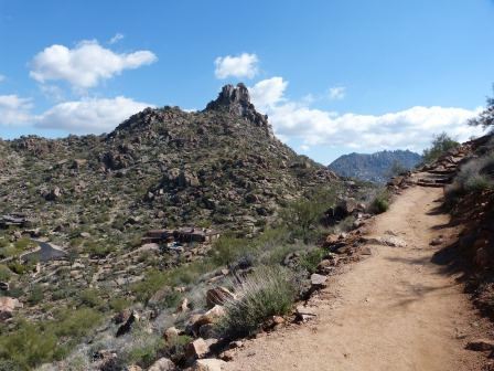 A rocky double peak with desert leading up to it and a dirt trail in the foreground