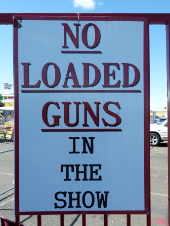 White sign with black letters saying :No Loaded Guns in the Show""