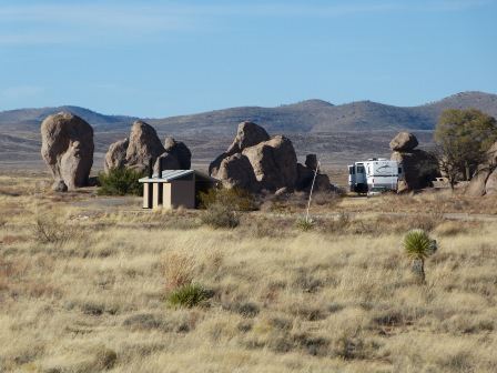 Large motorhome parked amonth the rocks with nearby bathrooms as viewed from across the desert
