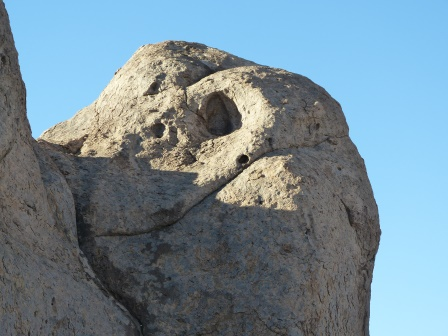 A grey rock against a blue background that may resemble a face to some