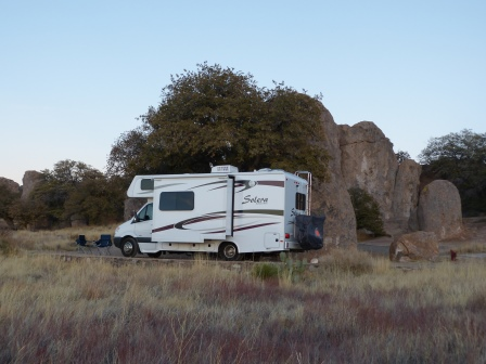 Our motorhome against a backdrop of rocks as viewed from acsross the desert