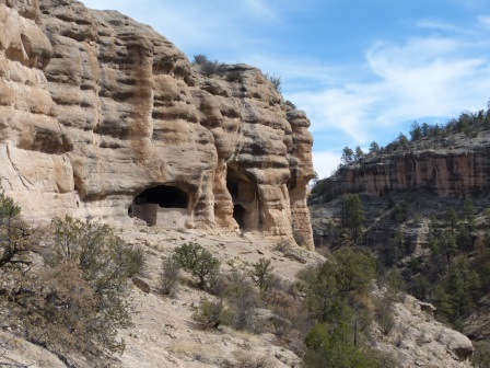 Large alcoves like caves in a brown cliff from a distance