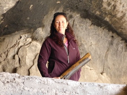 Diane's upper body wearning puple fleece visible over wall in a cave