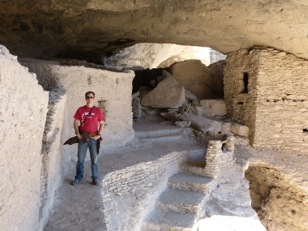 Patrick in red shirt and jeans standing on a walkway in Cave 4 & 5