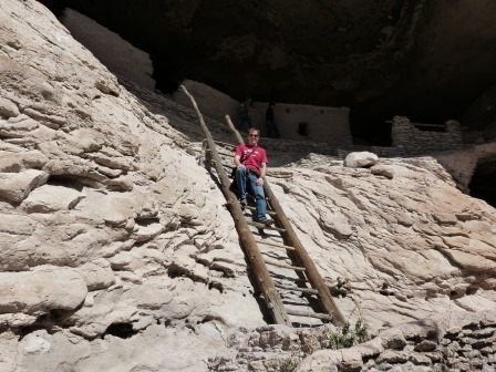 Patrick seated on a large wooden ladder made of poles that is exiting from a cave