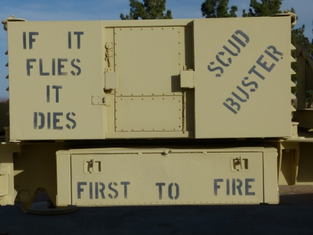 "Side of beige Patrior missile launcher with blank painted slogans ""Scud Buster"", If it Flies It Dies"", and ""First to Fire"""