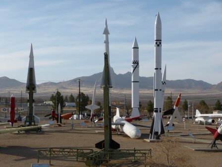 Many missiles, most standing, displayed in the desert