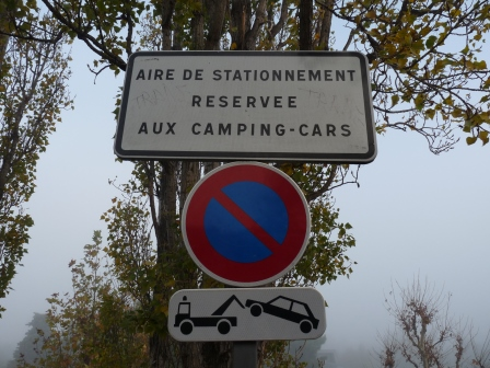 Sign saying 'Aire de Stationnement Reservee Aux Camping-Cars'  showing a picture of a car being towed awa