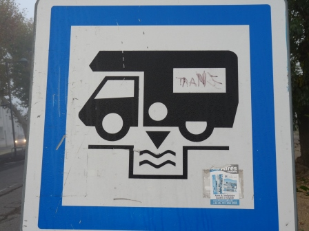A white sign with blue border showing a black motorhome dumping water below