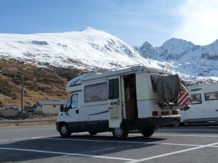 Our RV in a parking lot with snow and ski slopes in the background